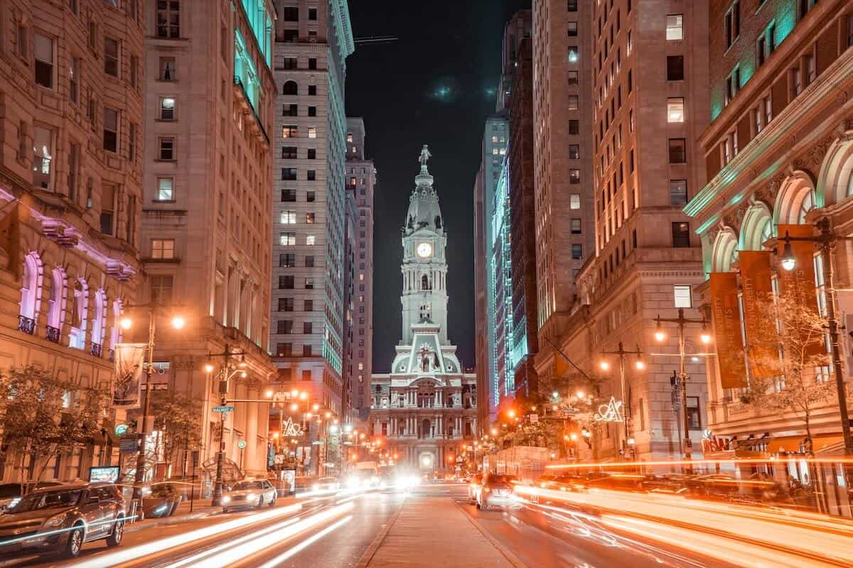 Reasons to Visit Philadelphia cover photo looking down North Broad Street to City Hall, the large while building lit up in the distance with light trails on each side of the street
