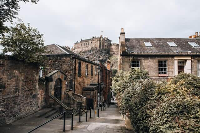 Vennel Steps leading down between two stone buildings with Edinburgh Castle on the hill in the background