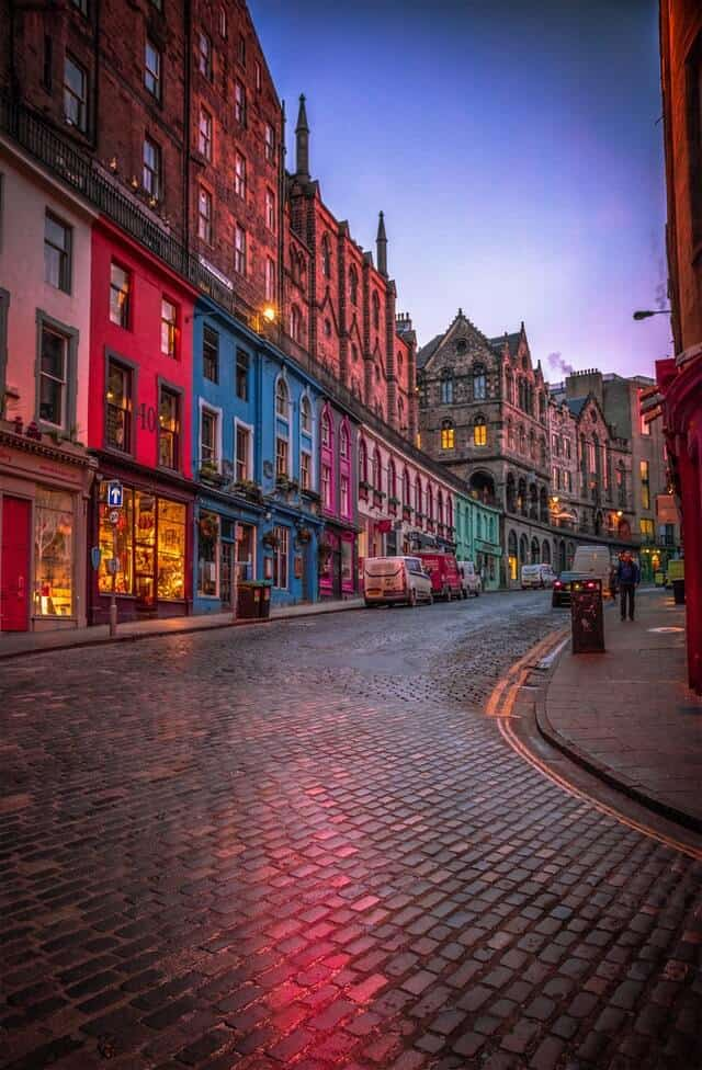 Curved and Cobbled Victoria Street, lined with colourful buildings light up at dusk