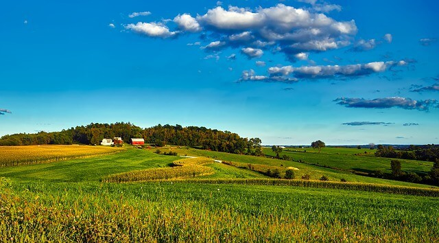 Redbarn building surrounded by green fields under a blue sky in Wisconsin