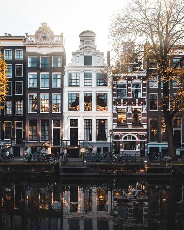 Tall skinny houses on the riverside in Amsterdam