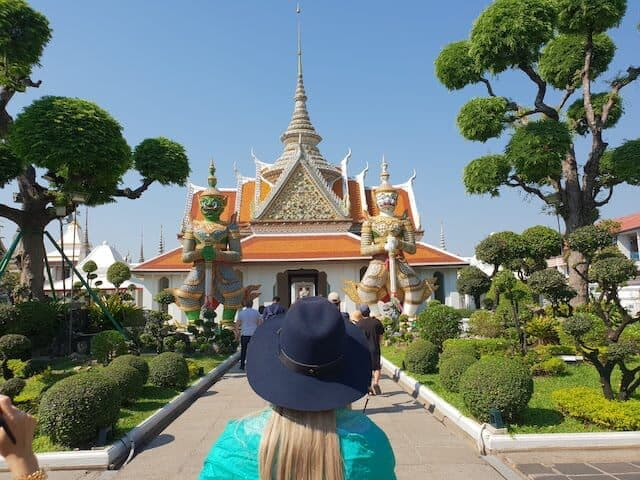 Woman in a blue hat and a green shawl standing in front of a gold temple in Bangkok