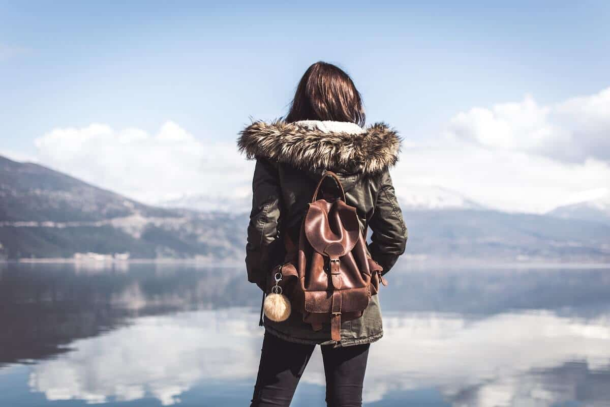 The Best Places to Travel Alone cover photo of a woman standing with her back to the camera carrying a brown leather sma;; backpack lookig out towads the lake in front of her