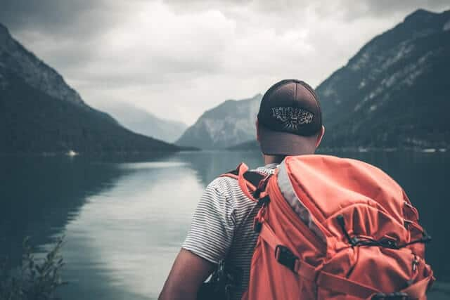 Man with a lrage orange backpack on his back, wearing a backwards facing baseball cap with his back to the camera looking a a lake surrounded by mountains